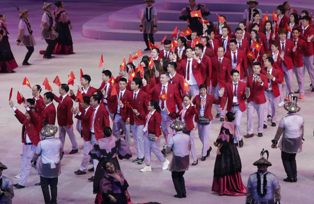 Vietnam's team wave flags during the opening ceremony of the 30th South East Asian Games at the Philippine Arena, Bulacan province, northern Philippines on Saturday, Nov. 30, 2019. (AP Photo/Aaron Favila)