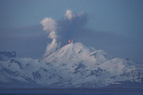 A lava fountain at the top of Alaska's Pavlof volcano, seen from Cold Bay on May 14, 2013. Steam and ash rise from the northwest slope as lava flows downward.