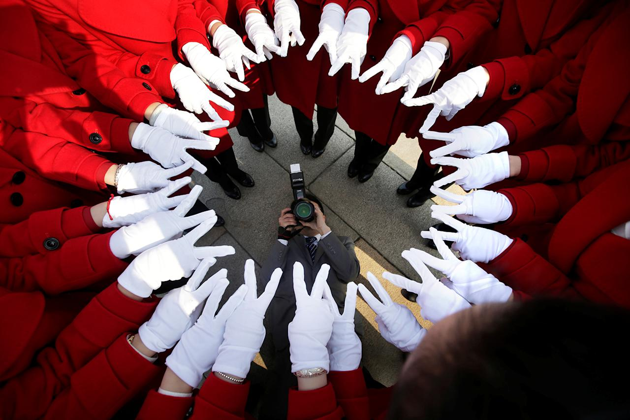 <p>Attendants serving delegates from a hotel pose for a photo at Tiananmen Square as delegates attend a meeting during the annual session of China's parliament, the National People's Congress (NPC), in Beijing, China on March 4, 2017. (Photo: Jason Lee/Reuters) </p>