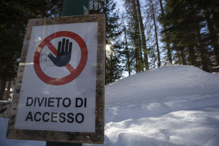 A No Entry sign is seen by the bobsled track in Cortina d'Ampezzo, Italy, Wednesday, Feb. 17, 2021. Bobsledding tradition in Cortina goes back nearly a century and locals are hoping that the Eugenio Monti track can be reopened for the 2026 Olympics in the Italian resort. (AP Photo/Gabriele Facciotti)