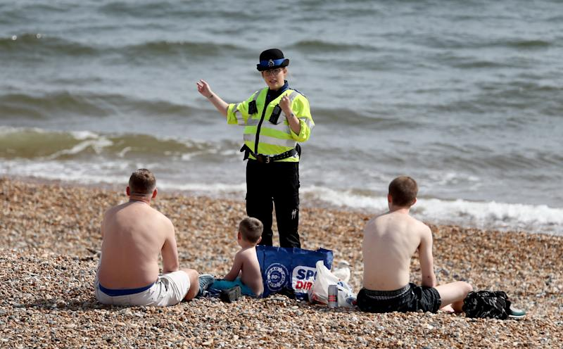 A police officer advises people to leave the beach during the warm weather in Brighton as the UK continues in lockdown to help curb the spread of the coronavirus. (Photo by Gareth Fuller/PA Images via Getty Images)