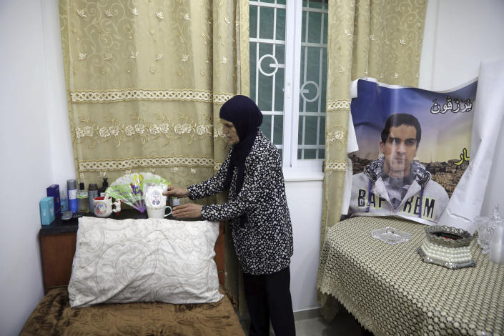 In this Wednesday, June 3, 2020 photo, Rana, mother of Eyad Hallaq, arranges his room in their home in East Jerusalem's Wadi Joz. Early Saturday, Hallaq, a 32-year-old Palestinian with severe autism, was chased by Israeli border police forces into a nook in Jerusalem's Old City and fatally shot as he cowered next to a garbage bin after apparently being mistaken as an attacker. He was just a few meters from his beloved Elwyn El Quds school. (AP Photo/Mahmoud Illean)