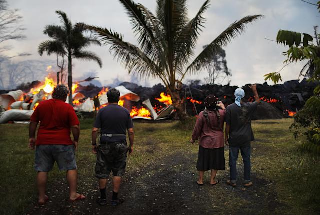 <p>Community members watch as a home is destroyed by lava from a Kilauea volcano fissure in Leilani Estates, on Hawaii's Big Island, on May 25, 2018 in Pahoa, Hawaii. (Photo: Mario Tama/Getty Images) </p>
