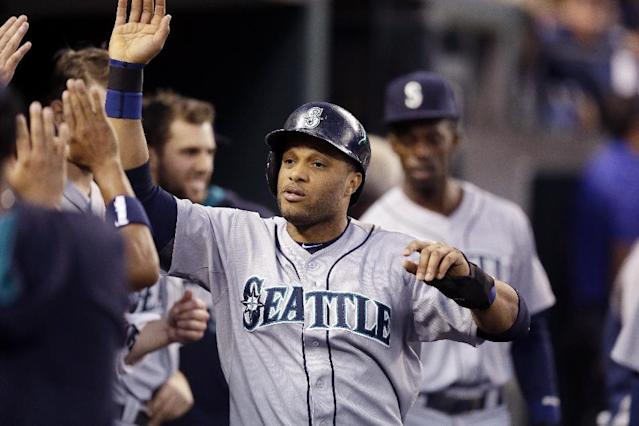 Seattle Mariners' Robinson Cano is congratulated in the dugout after scoring during the fifth inning of a baseball game against the Detroit Tigers, Friday, Aug. 15, 2014, in Detroit. (AP Photo/Carlos Osorio)