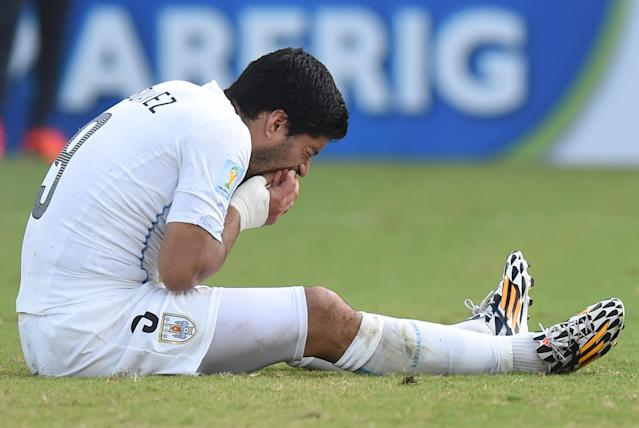Luis Suarez puts his hand to his mouth after clashing with Giorgio Chiellini during a football match between Italy and Uruguay in Natal during the 2014 FIFA World Cup on June 24, 2014 (AFP Photo/Javier Soriano)