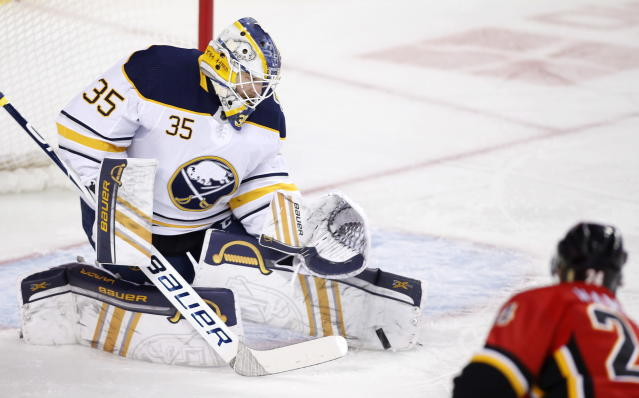 Buffalo Sabres goalie Linus Ullmark, from Sweden, makes a save against Calgary Flames Travis Hamonic during the first period of an NHL hockey game Thursday, Dec. 5, 2019, in Calgary, Alberta. (Larry MacDougal/The Canadian Press via AP)