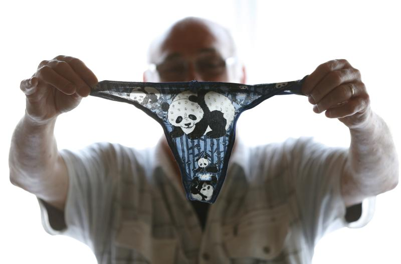 Andre Cornet holds a woman's underwear, part of a collection of about 2,200 pieces of panda collectables, in his house in Haccourt