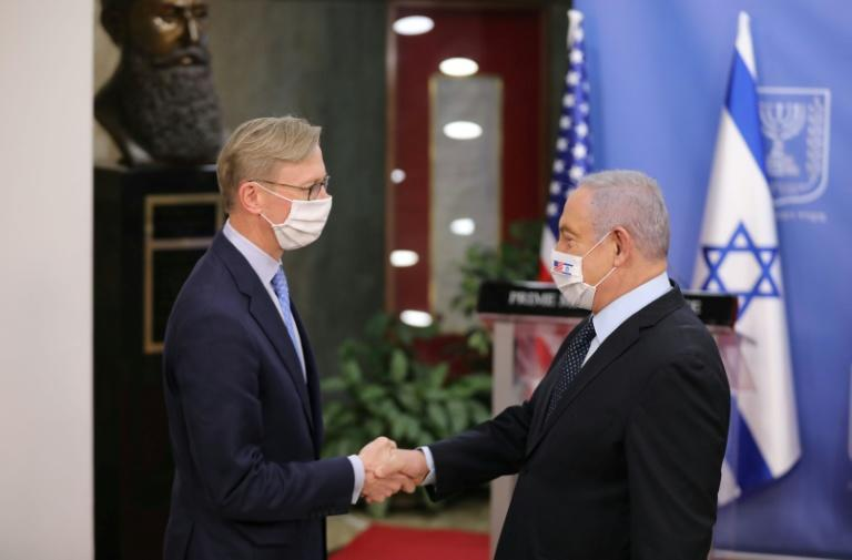 US special representative for Iran Brian Hook (L) and Israeli Prime Minister Benjamin Netanyahu (R), both wearing protective masks, shake hands at the premier's office in Jerusalem