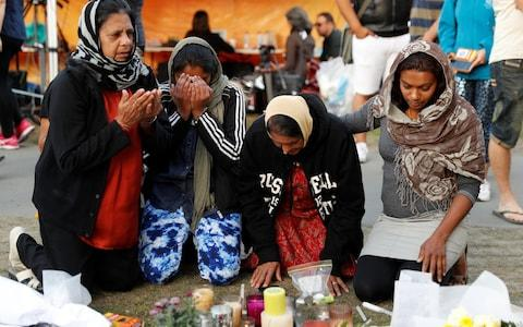 Family members from Fiji visit a memorial site for victims of Friday's shooting, in front of Christchurch Botanic Gardens in Christchurch - Credit: Reuters