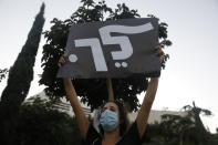 """A woman holds a placard that reads, """"go,"""" during a protest against Prime Minister Benjamin Netanyahu in Tel Aviv, Israel, Thursday, Oct. 8, 2020 during a nationwide lockdown to curb the spread of the coronavirus. The Israeli government has extended an emergency provision that bars public gatherings, including widespread protests against Netanyahu, for an additional week. (AP Photo/Ariel Schalit)"""