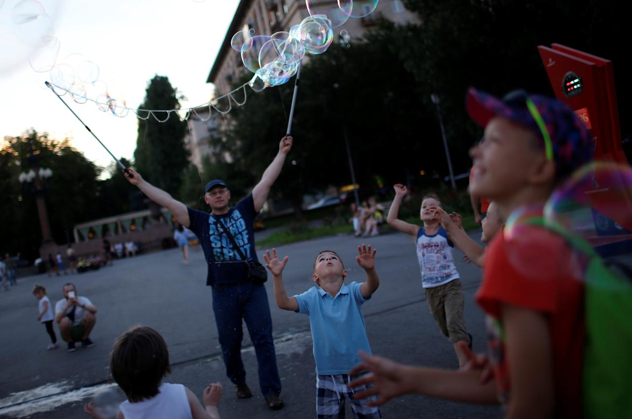 Children play with soap bubbles at the Victory park in Volgograd, Russia, July 22, 2017. REUTERS/David Mdzinarishvili
