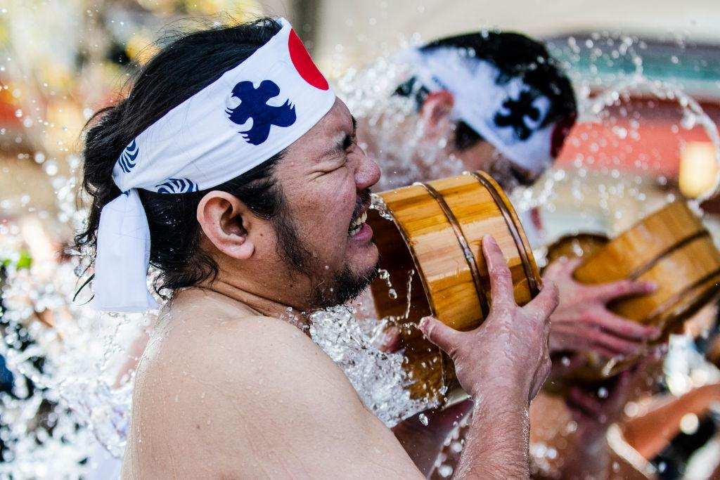 <p>A participant pours a bucket of cold water on himself during the annual New Year ice bath ceremony at Kanda Myojin Shinto on Jan. 26, 2019 in Tokyo, Japan. Participants wearing only shorts or loincloths pour cold water over themselves in a traditional ceremony to test their endurance as they believe it would purify their souls and bring them good luck. (Photo from Sawayasu Tsuji/Getty Images) </p>