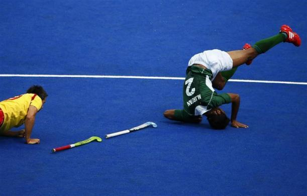 Spain's Pablo Amat (L) and Pakistan's Muhammad Irfan fall during their men's Group A hockey match at the London 2012 Olympic Games at the Riverbank Arena on the Olympic Park in London July 30, 2012.