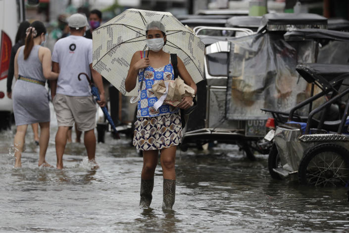 A woman wearing masks to prevent the spread of the coronavirus carries items as she wades along a flooded road due to Typhoon Molave in Pampanga province, northern Philippines on Monday, Oct. 26, 2020. A fast moving typhoon has forced thousands of villagers to flee to safety in provinces. (AP Photo/Aaron Favila)