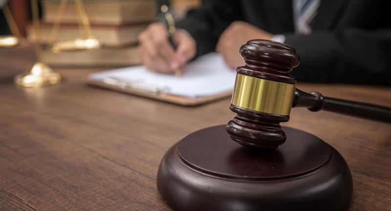 A West Australian woman has been jailed after setting fire to her partner's house, causing the death of two pets. Pictured is a stock image of a judge's gavel with a person dressed in a suit in the background.
