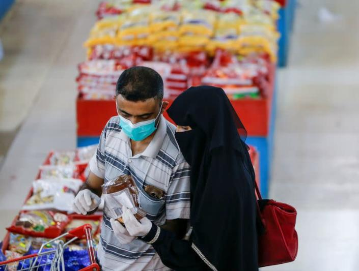 FILE PHOTO: Couple wearing protective face masks and gloves shop at a supermarket amid concerns of the spread of the coronavirus disease (COVID-19), in Sanaa