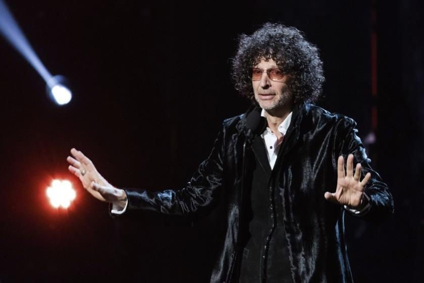 A man with bushy, curly hair in a shiny black suit speaks onstage