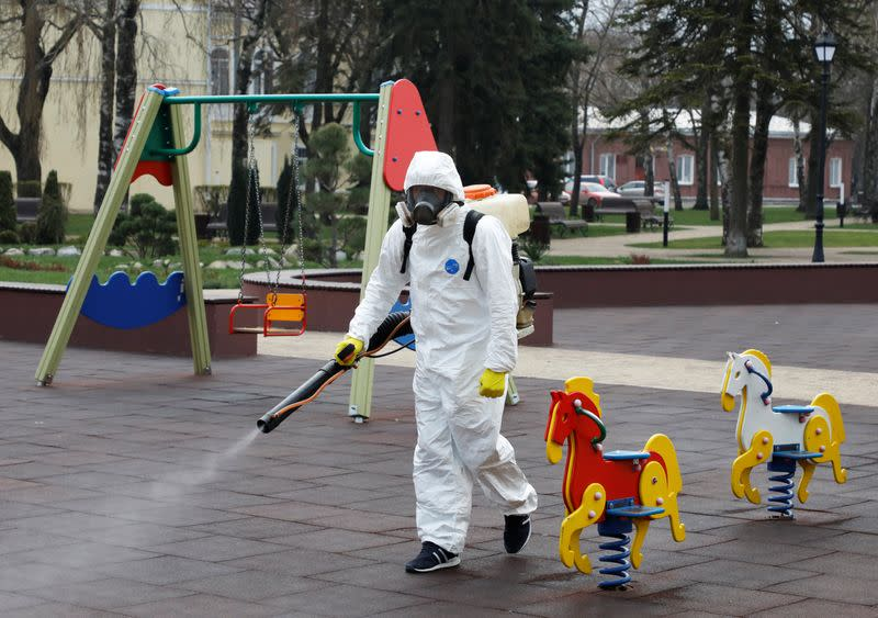A specialist sprays disinfectant while sanitizing a playground in Stavropol