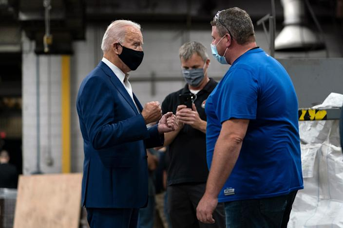 Democratic presidential candidate Joe Biden talks with workers as he tours the Wisconsin Aluminum Foundry in Manitowoc on Sept. 21, 2020.