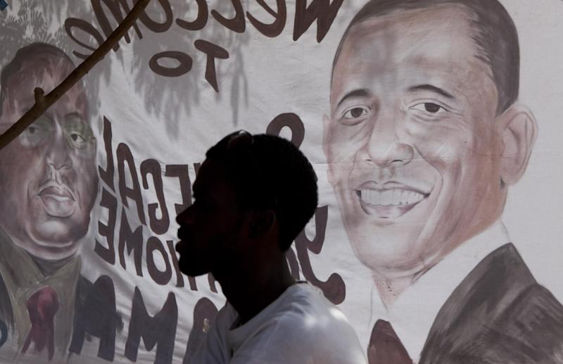 A man sits in the shade behind a banner depicting U.S. President Barack Obama and Senegalese President Macky Sall, and painted by artist Ouzin, in Dakar, Senegal, Wednesday, June 26, 2013. The U.S. President and his family arrive in Senegal Wednesday night to kick off a three-country African tour. (AP Photo/Rebecca Blackwell)