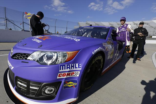 Denny Hamlin climbs out of his car during qualifying for Sunday's NASCAR Sprint Cup series auto race at Martinsville Speedway in Martinsville, Va., Friday, Oct. 25, 2013. Hamlin won the pole. (AP Photo/Steve Helber)