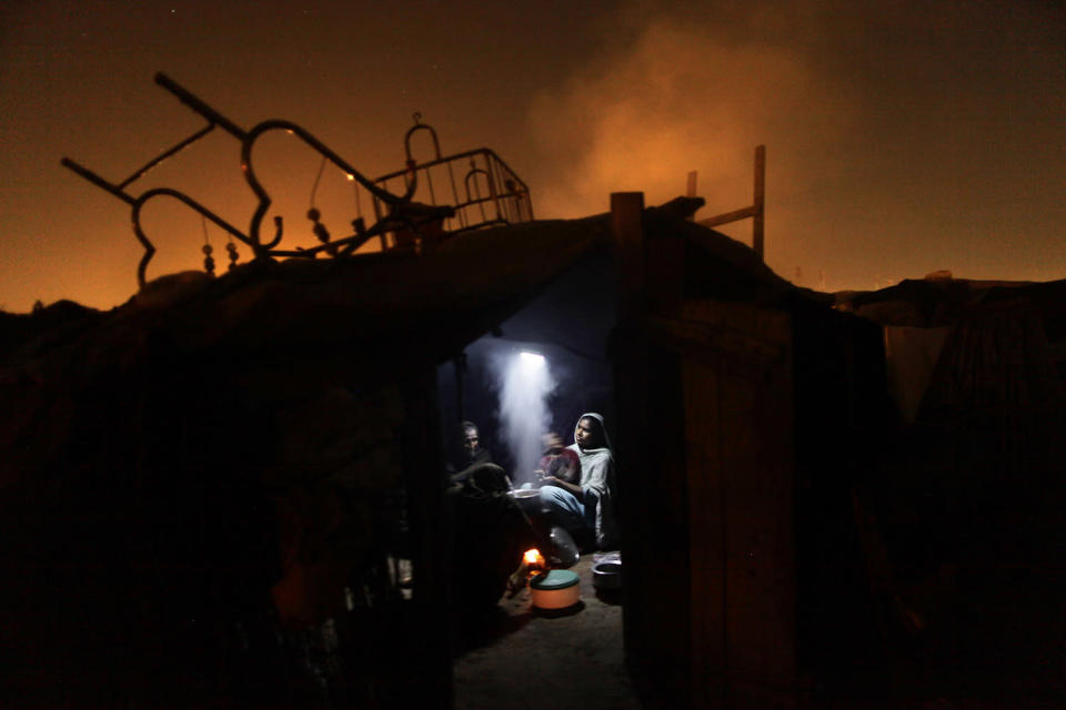 <p>Pakistani women cook for their family using a fire inside their makeshift home, in a slum in Islamabad, Pakistan, March 4, 2013. Slums which are built on illegal lands have neither running water or sewage disposal. (Photo: Muhammed Muheisen/AP) </p>