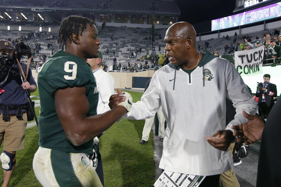 Michigan State coach Mel Tucker, right, congratulates Kenneth Walker III following an NCAA college football game against Western Kentucky, Saturday, Oct. 2, 2021, in East Lansing, Mich. Michigan State won 48-31. (AP Photo/Al Goldis)