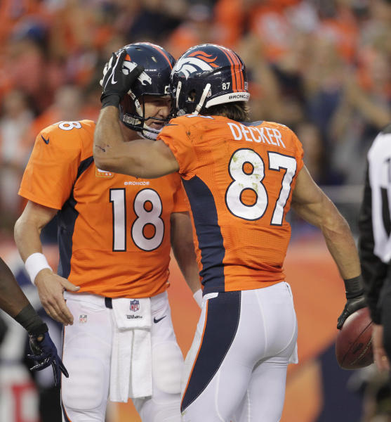Denver Broncos quarterback Peyton Manning (18) celebrates with wide receiver Eric Decker (87) after throwing a touchdown pass to Decker against the Oakland Raiders in the first quarter of an NFL football game, Monday, Sept. 23, 2013, in Denver. (AP Photo/Joe Mahoney)