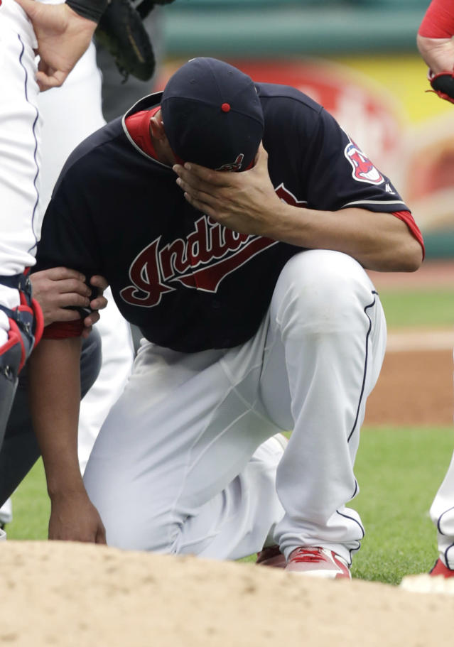 Cleveland Indians starting pitcher Carlos Carrasco waits on the mound after being hit by a ball on the arm as a trainer takes a look in the second inning of a baseball game against the Minnesota Twins, Saturday, June 16, 2018, in Cleveland. Carrasco left the game after the hit. (AP Photo/Tony Dejak)