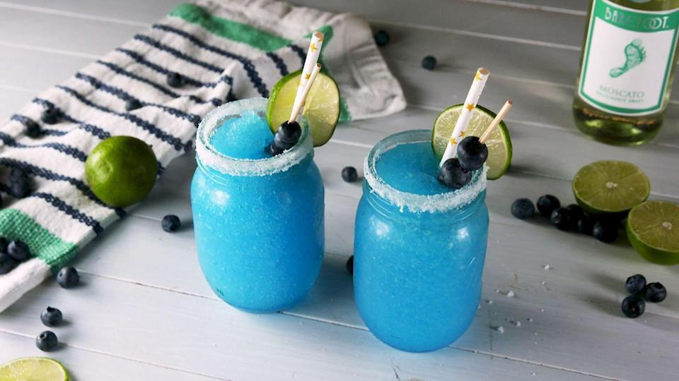 """<p>You can't celebrate the red, white, and blue without one of these frozen blue moscato margaritas in hand. </p><p><strong><em>Get the recipe at <a href=""""https://www.delish.com/cooking/recipe-ideas/a28568459/frozen-blue-moscato-margaritas-recipe/"""" rel=""""nofollow noopener"""" target=""""_blank"""" data-ylk=""""slk:Delish"""" class=""""link rapid-noclick-resp"""">Delish</a>. </em></strong></p>"""