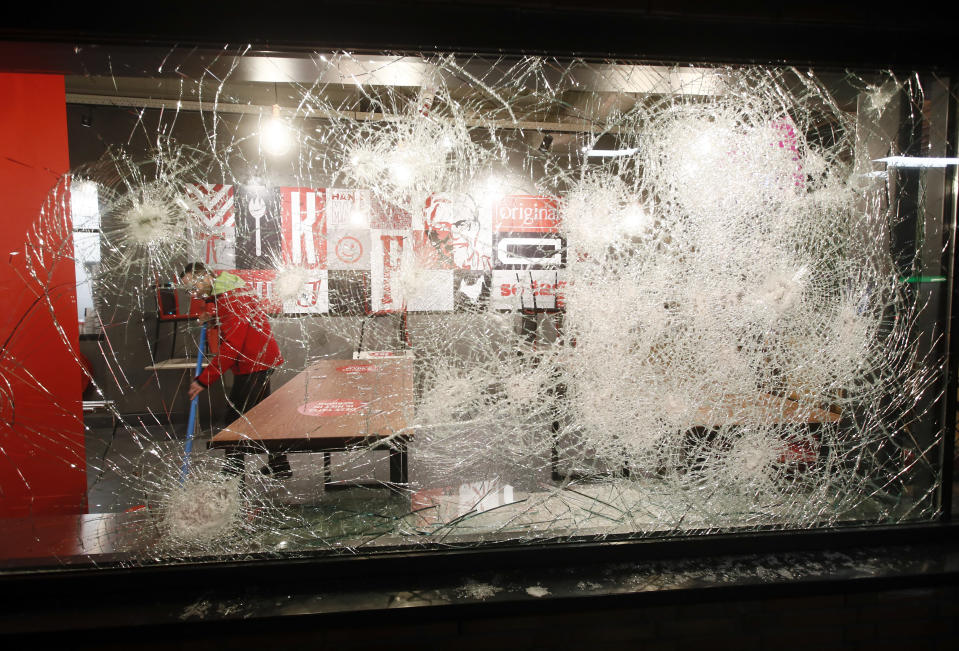 A man cleans up and is seen through the damaged glass in a fast-food restaurant that was smashed in protests against a nation-wide curfew in Rotterdam, Netherlands, Monday, Jan. 25, 2021. The Netherlands Saturday entered its toughest phase of anti-coronavirus restrictions to date, imposing a nationwide night-time curfew from 9 p.m. until 4:30 a.m. in a bid to control the COVID-19 infection rate. (AP Photo/Peter Dejong)