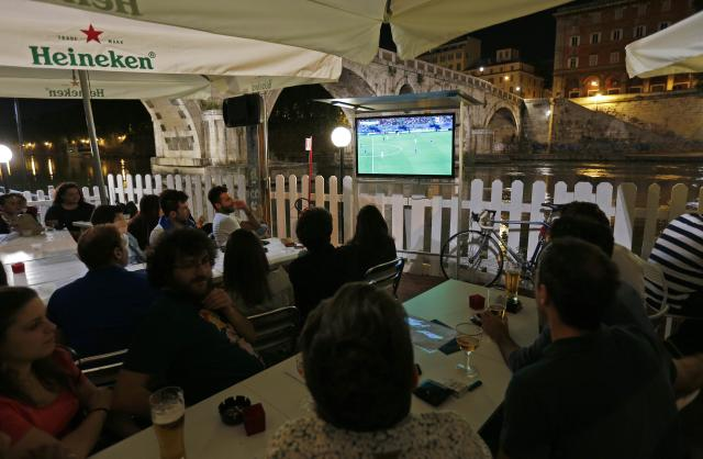 People watch England vs Italy soccer match during the 2014 World Cup in a pub on the Tiber river in Rome June 14, 2014. REUTERS/Max Rossi (ITALY - Tags: SPORT SOCCER WORLD CUP SOCIETY)
