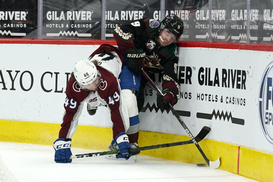 Colorado Avalanche defenseman Samuel Girard (49) and Arizona Coyotes right wing Clayton Keller battle for the puck in the second period during an NHL hockey game, Tuesday, March 23, 2021, in Glendale, Ariz. (AP Photo/Rick Scuteri)