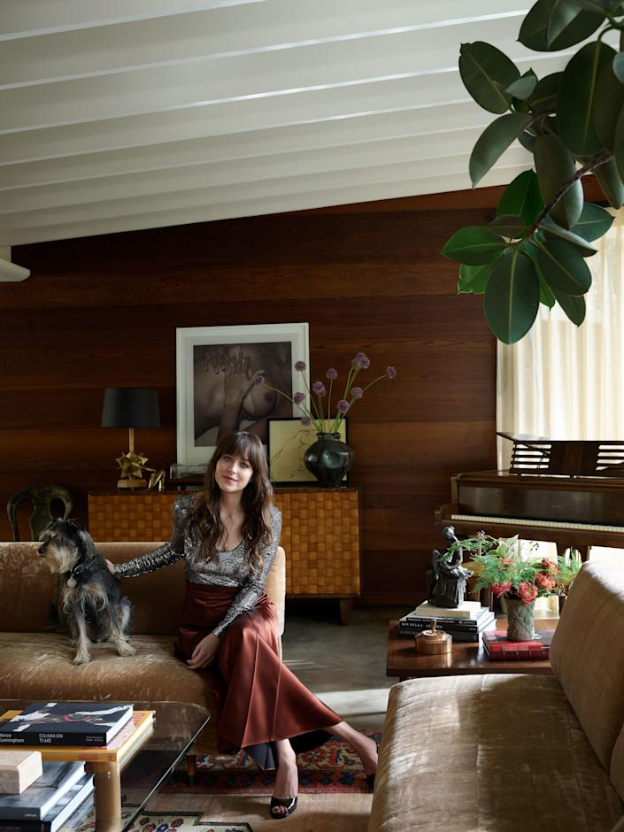 Johnson, in a Gucci bodysuit and skirt, sits with Zeppelin on an antique sofa in the living room.