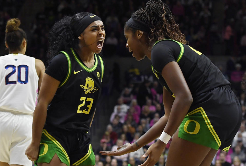 Oregon's Minyon Moore (23) reacts toward teammate Oregon's Ruthy Hebard, right, in the first half of an NCAA college basketball game against Connecticut, Monday, Feb. 3, 2020, in Storrs, Conn. (AP Photo/Jessica Hill)