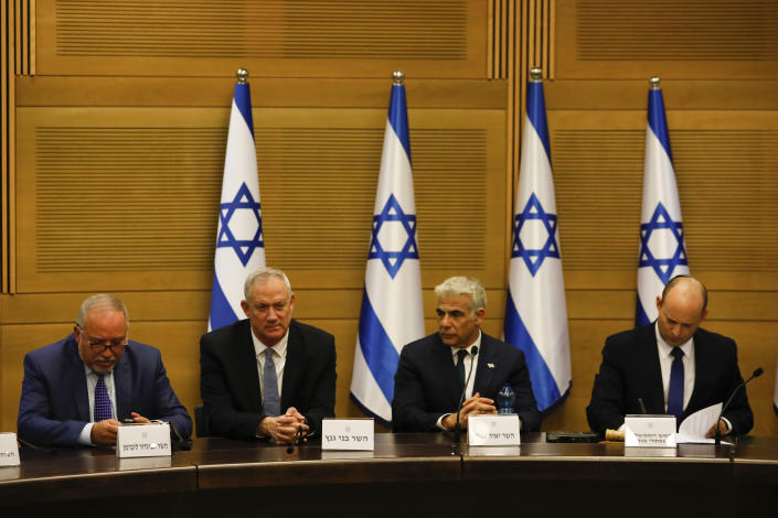 FILE - In this Sunday, June 13, 2021, file photo, Avigdor Lieberman, from left, Benny Gantz, Yair Lapid and Israel's new prime minister Naftali Bennett hold a first cabinet meeting in Jerusalem. Israel's parliament is set to vote Monday, July 5, 2021, on whether to renew a temporary law first enacted in 2003 that bars Arab citizens of Israel from extending citizenship or even residency to spouses from the occupied West Bank and Gaza. (AP Photo/Ariel Schalit, File)