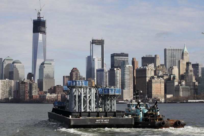 A barge loaded with sections of spire for One World Trade Center, left, is guided by tugboat across New York Harbor from New Jersey's Port Newark, Tuesday, Dec. 11, 2012 in New York. The spire is expected to rise into the Manhattan sky by spring. (AP Photo/Mark Lennihan)
