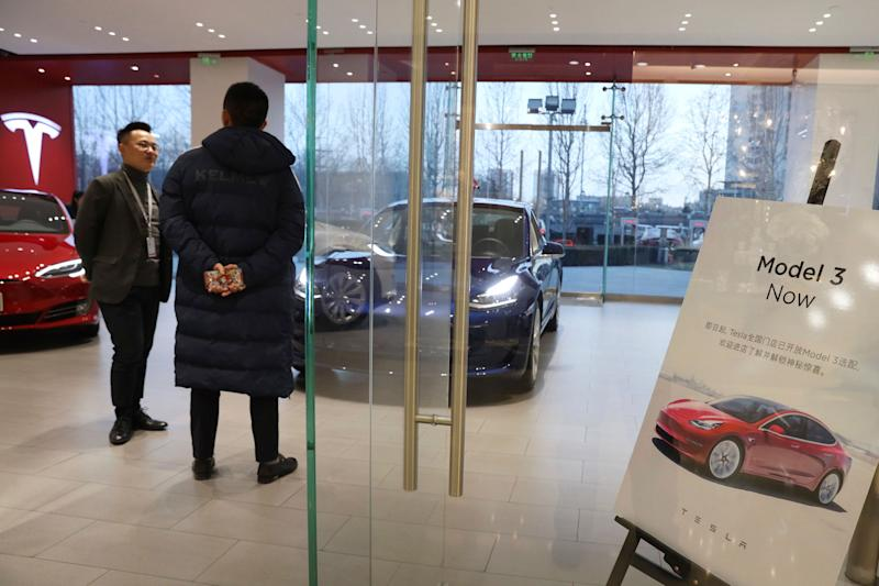 A sales staff chats with a customer at a Tesla store near a poster announcing orders of the Model 3 electric cars in Beijing, China, Monday, Jan. 7, 2019. Tesla Motors CEO Elon Musk said Monday on Twitter that the automaker is breaking ground for a Shanghai factory and will start production of its Model 3 by the end of the year. (AP Photo/Ng Han Guan)