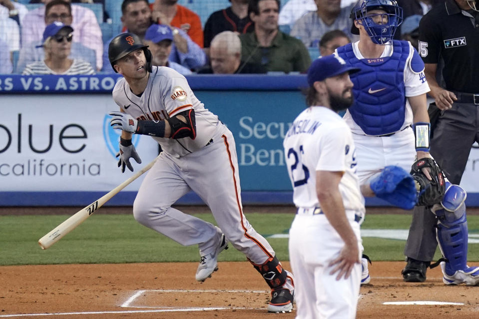 San Francisco Giants Buster Posey, left, runs to first as he hits a two-run home run while Los Angeles Dodgers starting pitcher Tony Gonsolin, center and catcher Will Smith watch during the first inning of a baseball game Monday, July 19, 2021, in Los Angeles. (AP Photo/Mark J. Terrill)