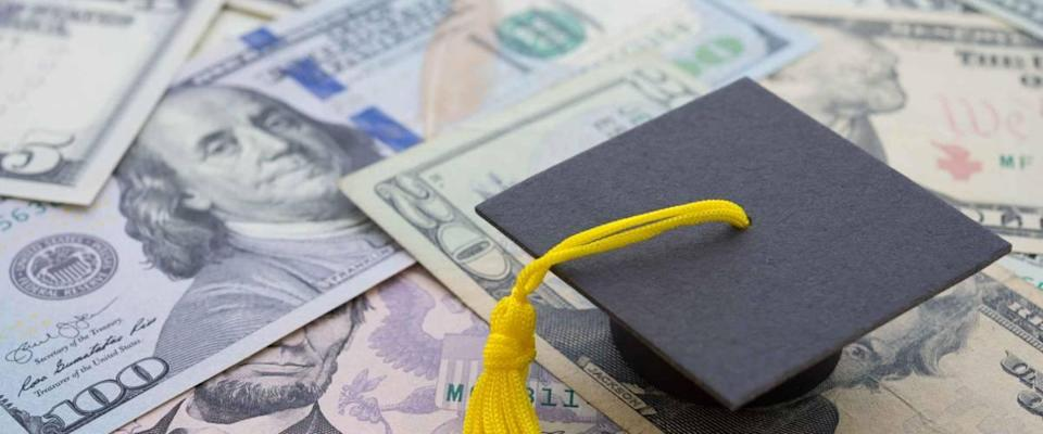University or college graduation cap on the background of US dollars banknotes.  Education spending budget plan for money saving, loan, debt, loan
