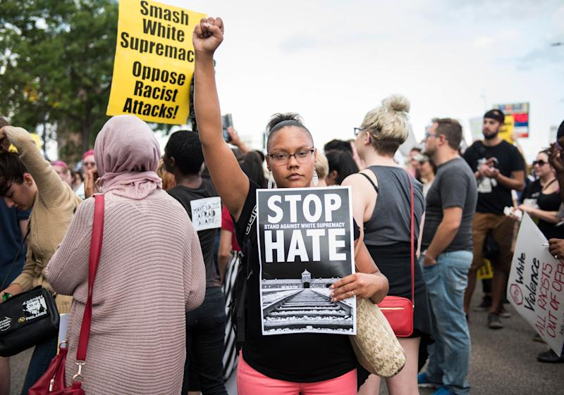 A woman raises her fist at the front of a march down Washington Avenue to protest racism and the violence over the weekend in Charlottesville, Virginia.