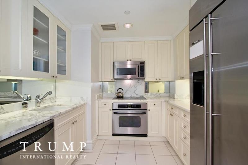 The kitchen has white marble counters and floors. (Photo source: Trump International Realty New York via StreetEasy listing)