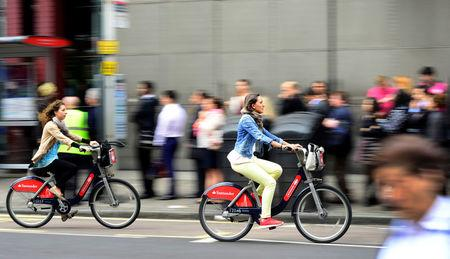 FILE PHOTO - Commuters cycle past a bus queue outside Waterloo Station in London