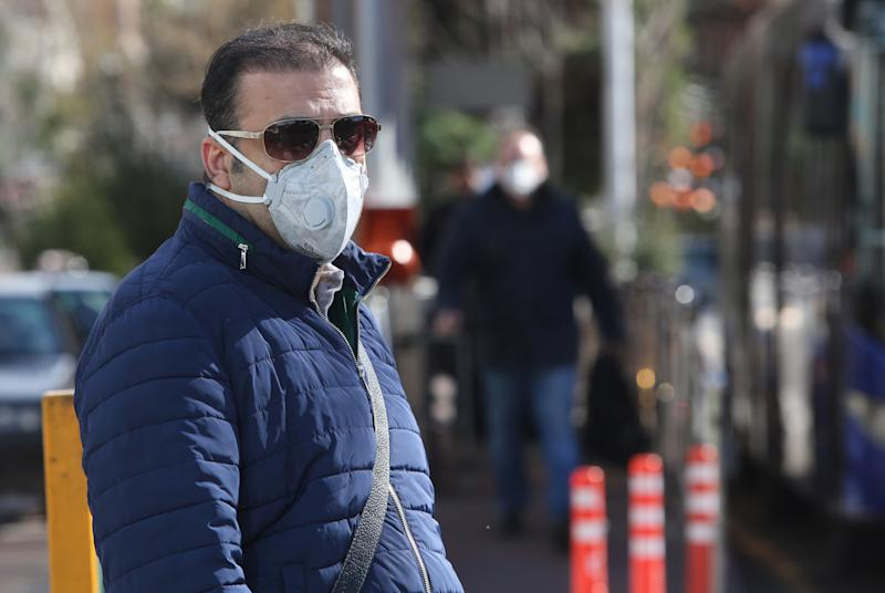 An Iranian man is pictured wearing a protective mask in Vanak square in the Iranian capital Tehran on March 2, 2020, following the COVID-19 illness outbreak, which Iran says has claimed 66 lives out of 1,501 cases of infection in the Islamic republic since February. - The novel coronavirus has sparked intense debate in Iran between ultra-conservative Shiite clerics and the government on how to most effectively tackle the deadliest outbreak of the disease outside China. (Photo by ATTA KENARE / AFP) (Photo by ATTA KENARE/AFP via Getty Images)