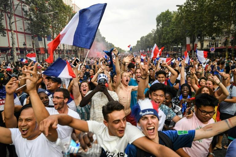 French fans on the Champs-Elysees avenue in Paris celebrate the World Cup win