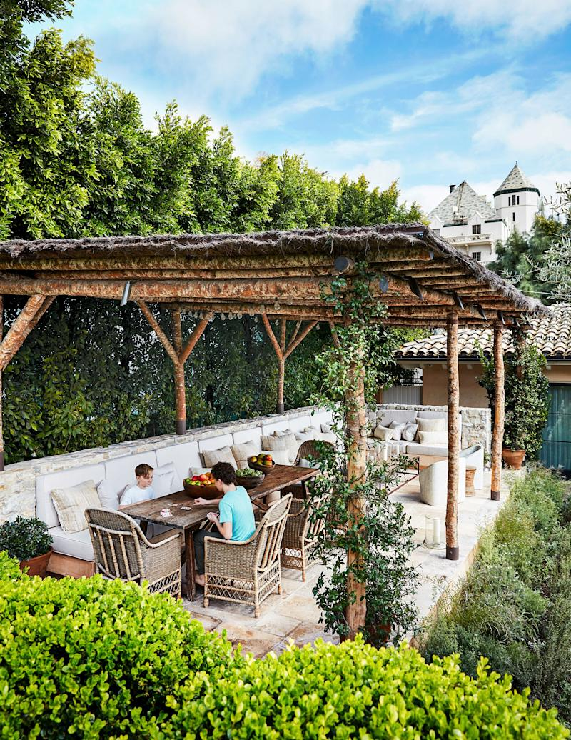 The Misczynskis' sons, Henry (left) and Miles, play cards in the pergola, whose design was inspired by the Castiglion del Bosco estate in Tuscany. Landscape design by Hoffman and Ospina Landscape Architecture.