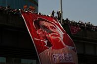 Protesters stand with a huge banner of detained Myanmar leader Aung San Suu Kyi as they take part in a demonstration against the military coup in Yangon