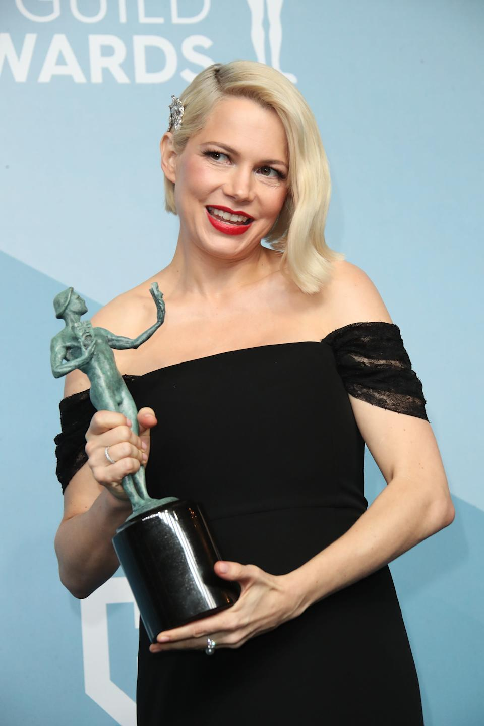 """Michelle Williams poses in the press room with the award for outstanding performance by a female actor in a television movie or miniseries for """"Fosse/Verdon""""."""