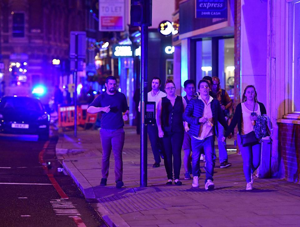 """<p>People run down Borough High Street as police are dealing with a """"major incident"""" at London Bridge. (Dominic Lipinski/PA via AP) </p>"""