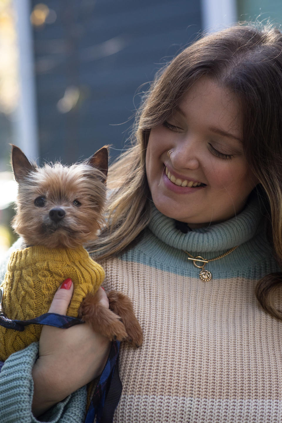 """Kursten Hedgis holds her dog Bitsy in front of her home Dec. 9, 2020, in Decatur, Ga. Bitsy is 14 and has been with her six years after a life as a breeder in a puppy mill. He is blind in one eye and suffers periodic infections and incontinence. Trips to the veterinarian have been """"really scary"""" because of the masks and reduced contacts. However, Hedgis and other pet owners say they have become more than companions in recent months, that they provide valuable emotional support to their humans. (AP Photo/Ron Harris)"""